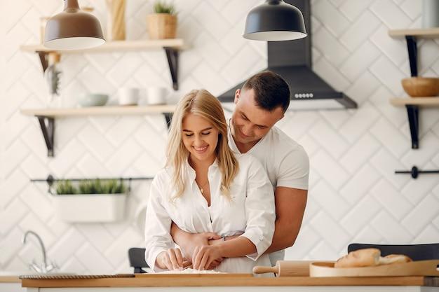 Het mooie paar bereidt voedsel in een keuken voor Gratis Foto