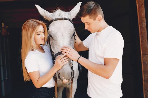Het mooie paar brengt tijd met paarden door Gratis Foto