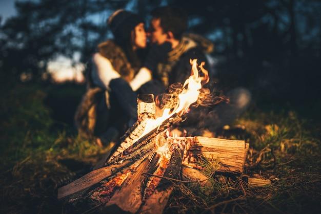 Het mooie paar ontspannen dichtbij vuur in het bos in avondtijd Premium Foto