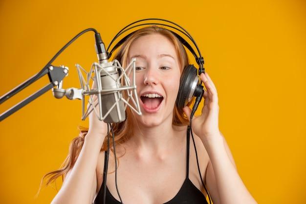 Het mooie roodharige vrouwengezicht zingen met een condensator zilveren microfoon die open mond lied uitvoeren stelt over de gele ruimte van het muurexemplaar voor uw tekst. fm-radio-omroeper. Premium Foto