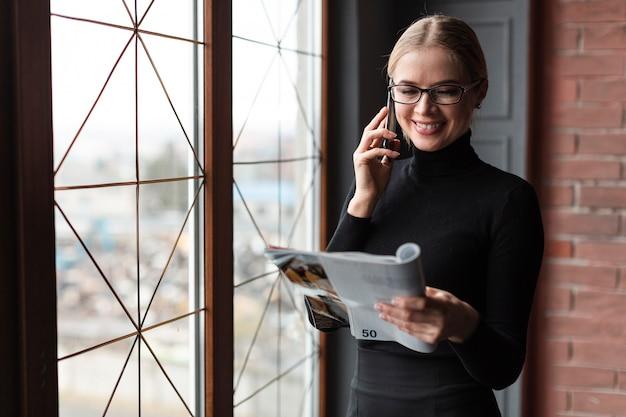 Het mooie tijdschrift van de vrouwenlezing en het spreken over telefoon Gratis Foto
