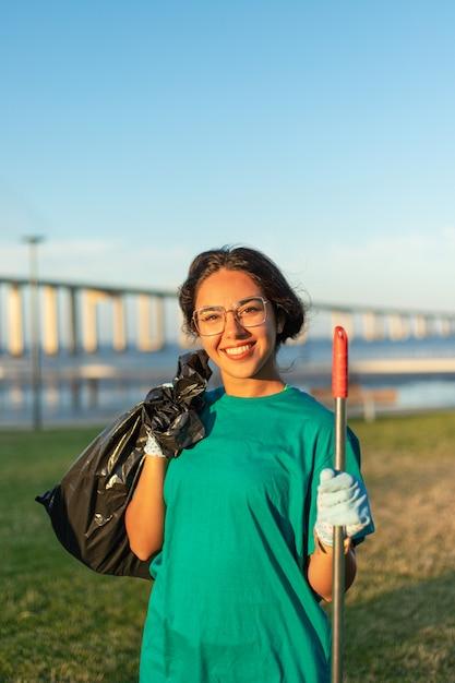 Het mooie vrijwilligersvrouw stellen in stadspark Gratis Foto