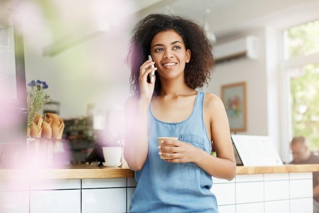 Het mooie vrolijke jonge afrikaanse studente glimlachen die op telefoon het drinken koffie in koffie spreken. Gratis Foto