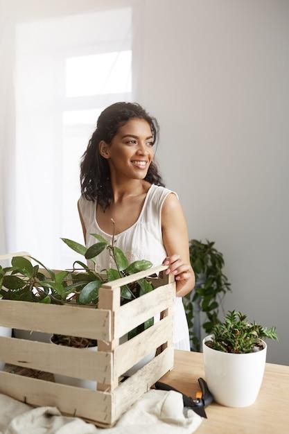 Het mooie vrouw glimlachen die met installaties in doos op het werk werken witte muur. Gratis Foto