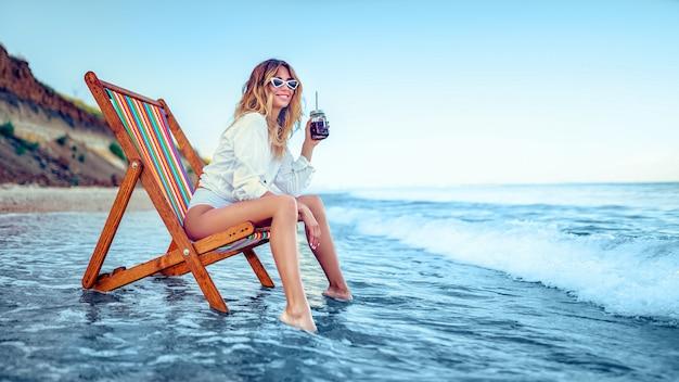 Het mooie vrouw ontspannen op een ligstoelstrand en drinkt sodawater. zomervakantie concept Premium Foto