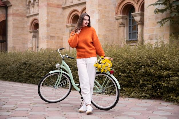 Het mooie vrouw stellen met buiten fiets en bloemen Gratis Foto