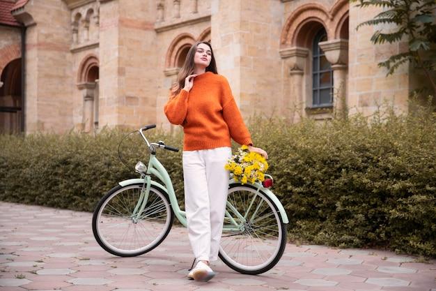 Het mooie vrouw stellen naast fiets buiten Gratis Foto