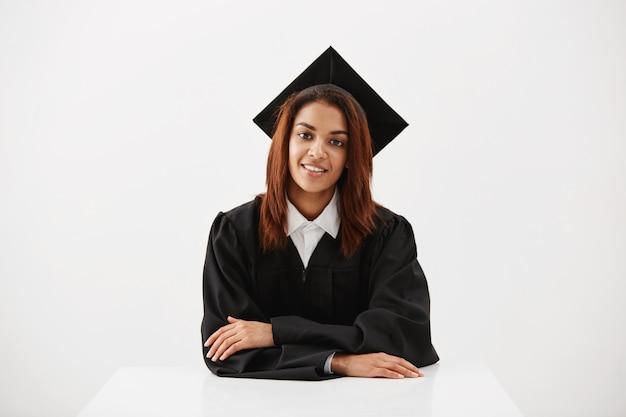 Het mooie vrouwelijke gediplomeerde glimlachen die camerazitting bekijken over witte oppervlakte Gratis Foto
