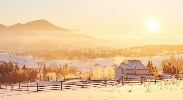 Het mysterieuze winterlandschap bestaat in de winter uit majestueuze bergen. fantastische zonsondergang. huizen opnemen in de sneeuw. foto beleefdheid briefkaart. karpaten Premium Foto