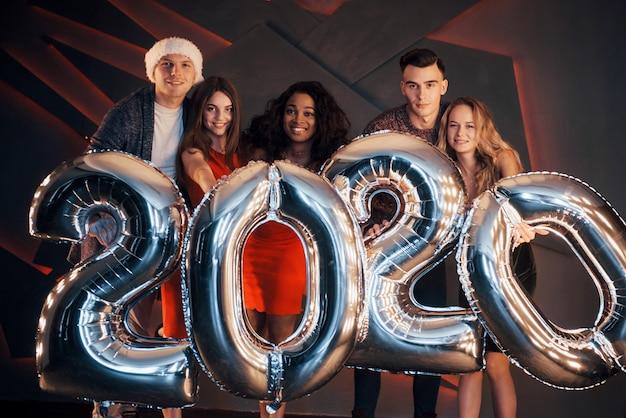Het nieuwe 2020-jaar komt eraan. groep leuke jonge multinationale mensen op een feestje. gelukkig nieuwjaar Premium Foto