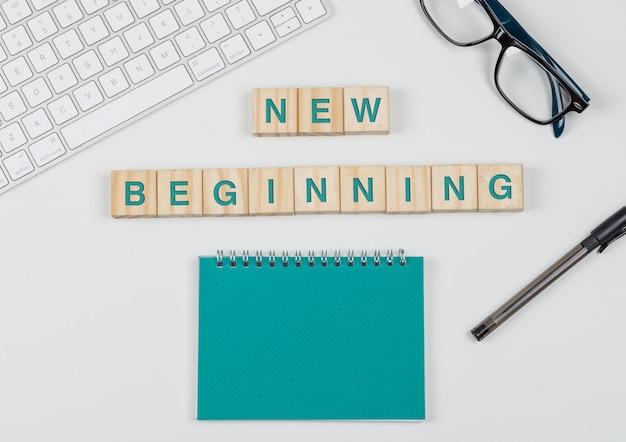 Het nieuwe begin en bedrijfsconcept met houten blokken, glazen, toetsenbord, pen, notitieboekje op witte vlakte als achtergrond lag. Gratis Foto