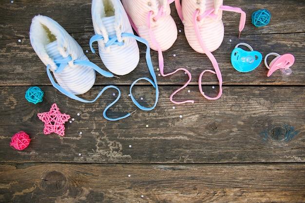 Het nieuwe jaar van 2020 geschreven veters van kinderschoenen en fopspeen op oude houten achtergrond Premium Foto