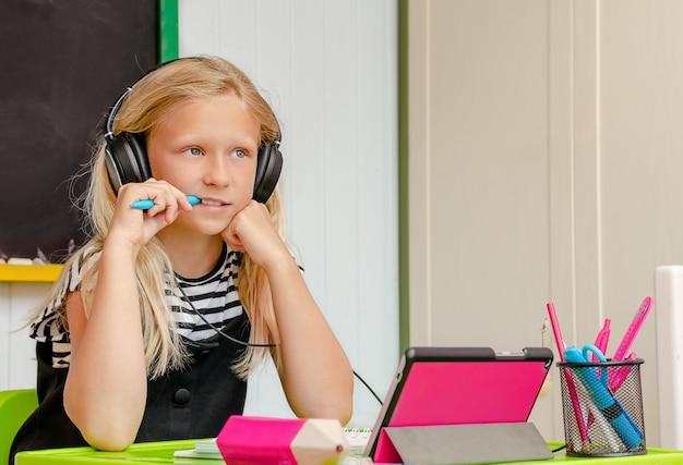 Het nieuwsgierige blondemeisje met oortelefoons is bij huisonderwijs. online cursus en onderwijsconcept Premium Foto