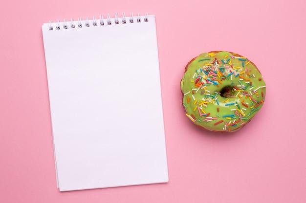 Het notitieboekje en de zoete groene doughnut met bestrooien op een roze vlakte als achtergrond leggen Premium Foto