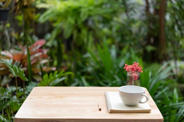 Het notitieboekje van de koffiekop, bruin potlood en mooie rode droge bloem in glasvaas op houten lijst Premium Foto