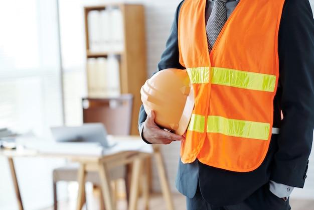 Het onherkenbare mannelijke bouwnijverheids uitvoerende stellen in veiligheidsvest, met bouwvakker Gratis Foto