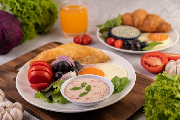 Het ontbijt bestaat uit brood, gebakken ei, slasaus, zwarte druiven, tomaten en gesneden uien. Gratis Foto
