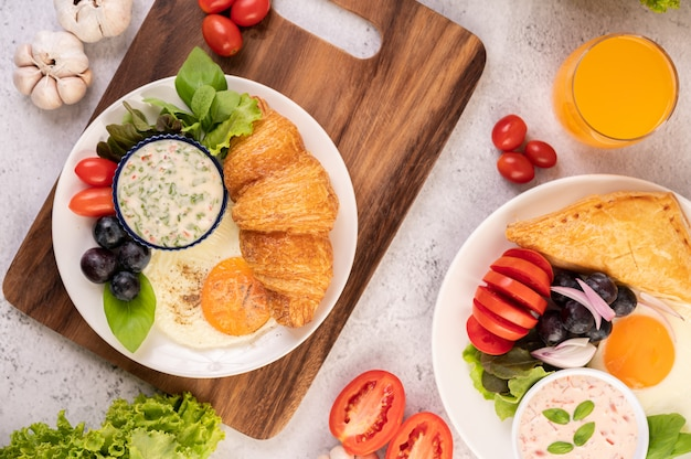 Het ontbijt bestaat uit croissant, gebakken ei, slasaus, zwarte druiven en tomaten. Gratis Foto