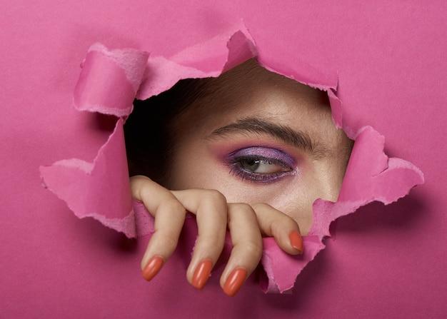 Het oog van het meisje met make-up in een gescheurd roze document gat. Premium Foto