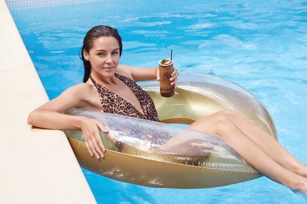 Het openluchtschot van jonge donkerbruine vrouw die met nat haar ontspannen op opblaasbaar zwemt ring, dragend manier swimwear met luipaarddruk, meisje geniet van coctails in zwembad tijdens de zomervakantie. Premium Foto