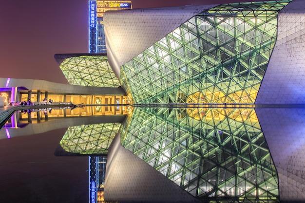 Het operahuis van guangzhou en bezinning over het water bij nachtlandschap Premium Foto