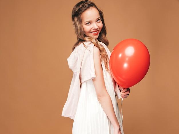 Het opgewekte jonge meisje stellen in trendy de zomer witte kleding. vrouwenmodel met het rode ballon stellen. klaar om te feesten Gratis Foto