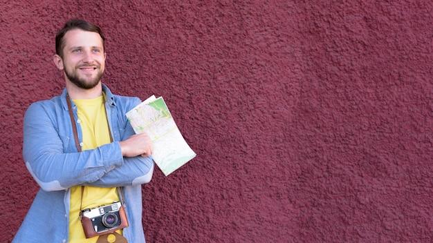 Het overwegen van jonge glimlachende de holdingskaart die van de reizigersfotograaf zich dichtbij geweven muurachtergrond bevinden Gratis Foto