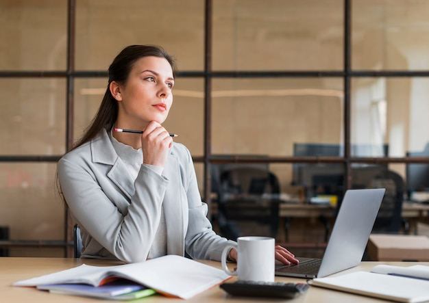 Het overwegen van onderneemsterzitting voor laptop in bureau Premium Foto