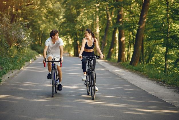 Het paar berijdende fietsen van sporten in de zomerbos Gratis Foto