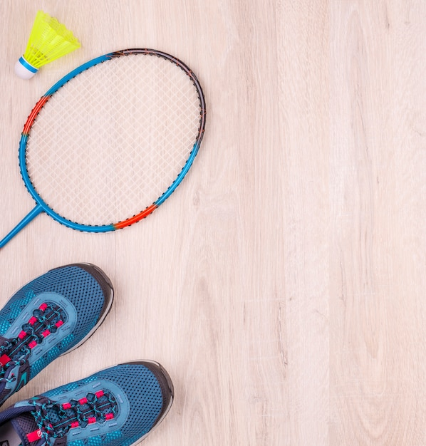 Het paar blauwe damessneakers, badmintonracket en shuttle op wit houten oppervlak Premium Foto