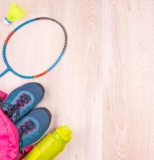 Het paar blauwe damessneakers en fles in roze rugzak, badmintonracket en shuttle op wit houten oppervlak Premium Foto