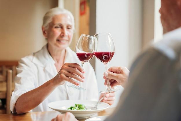 Het paar clinking glazen van de close-up met rode wijn Gratis Foto