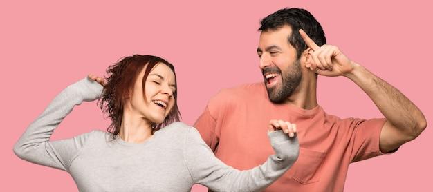 Het paar in valentijnskaartdag geniet van dansend terwijl het luisteren aan muziek op een partij over geïsoleerde roze achtergrond Premium Foto