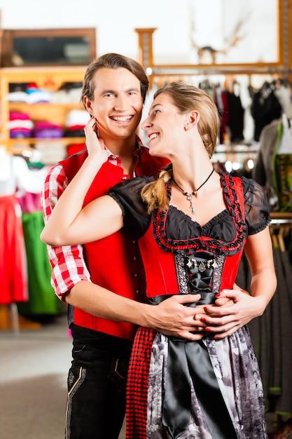 Het paar probeert dirndl of lederhosen in een winkel Premium Foto