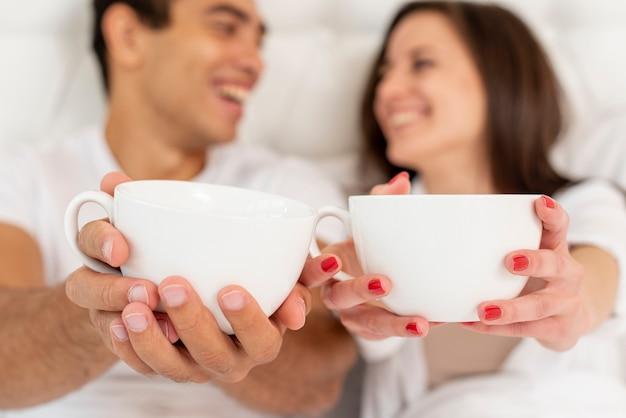 Het paar van close-upsmiley met koffiekoppen Gratis Foto