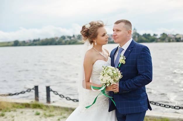 Het paar wed omhelst en kust dichtbij water Premium Foto