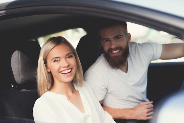 Het paar zit in de cabine van een comfortabele elektrische auto Premium Foto