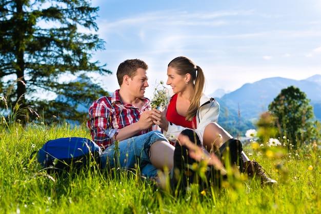 Het paar zit in de weide met berg Premium Foto