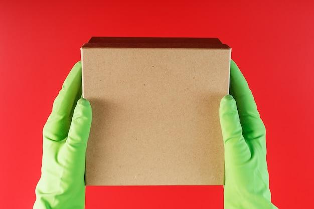 Het pakket van de bezorgdienst in de handen met groene rubberen handschoenen op een rode achtergrond. Premium Foto