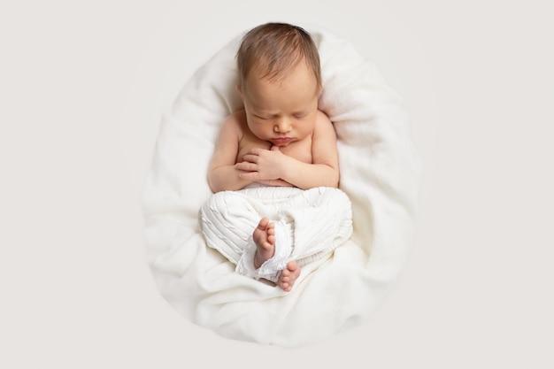 Het pasgeboren babymeisje slaapt in de mand op een witte deken en een licht Premium Foto