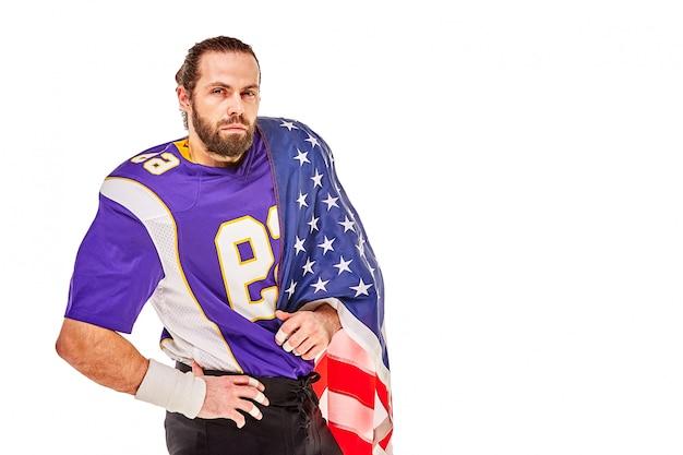Het patriottische amerikaanse voetbalster stellen bij camera op witte achtergrond met de vlag van de vs het concept van patriottisme, oproep tot actie, sportbanner van amerikaans voetbal. Premium Foto