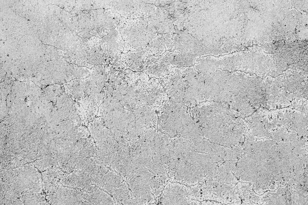 Het patroon van een grijze betonnen muur met krullende scheuren Gratis Foto