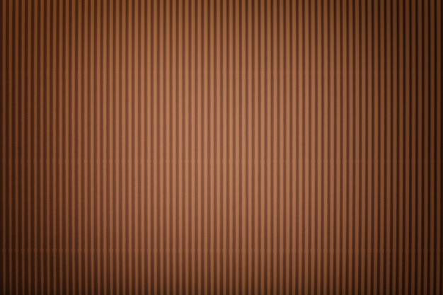 Het patroon van gegolfd donker bruin papier met vignet, macro. gestreepte bronzen kartonnen achtergrond, close-up. Premium Foto