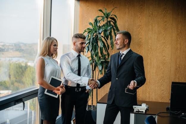 Het personeel op kantoor om zakelijke zaken naast het raam te bespreken. bedrijfsfinanciering Premium Foto