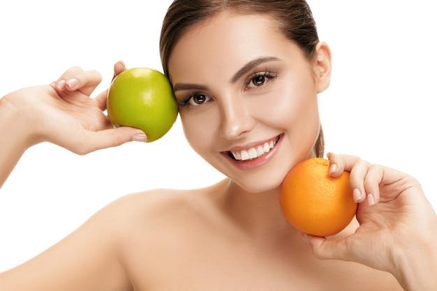 Het portret van aantrekkelijke kaukasische glimlachende vrouw die op witte studiomuur wordt geïsoleerd met groene appel en oranje vruchten. het concept van schoonheid, verzorging, huid, behandeling, gezondheid, spa, cosmetica en advertentie Gratis Foto