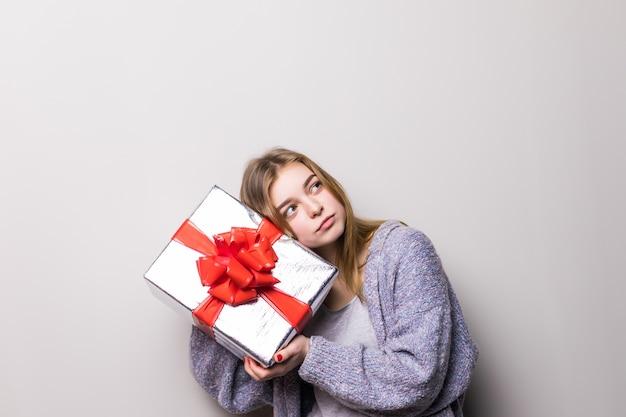 Het portret van de aanwezige holding van het tienermeisje en luistert in geïsoleerde doos Gratis Foto