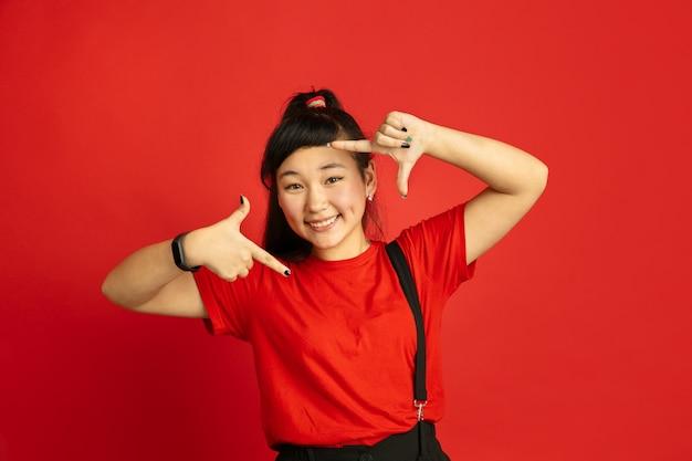 Het portret van de aziatische tiener dat op rode studioachtergrond wordt geïsoleerd. mooi vrouwelijk donkerbruin model met lang haar in informele stijl. concept van menselijke emoties, gezichtsuitdrukking, verkoop, advertentie. selfie inlijsten. Gratis Foto