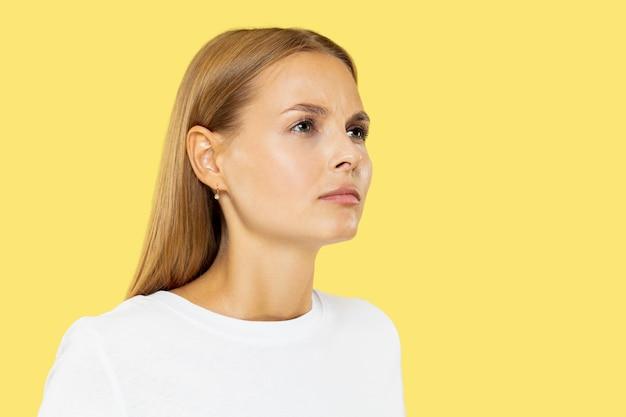 Het portret van de halve lengte van de kaukasische jonge vrouw op gele studio Gratis Foto