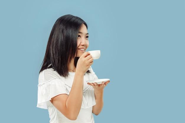 Het portret van de halve lengte van de koreaanse jonge vrouw op blauwe studio Gratis Foto