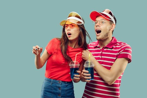Het portret van de halve lengte van het mooie jonge paar geïsoleerd. glimlachende vrouw en man in caps en zonnebril met drankjes. gelaatsuitdrukking, zomer, weekendconcept. trendy kleuren. Gratis Foto